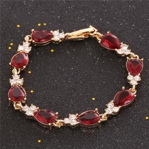 Праздничный браслет «Презент» с красными камнями в форме капли в оправе с покрытием под золото фото. Купить