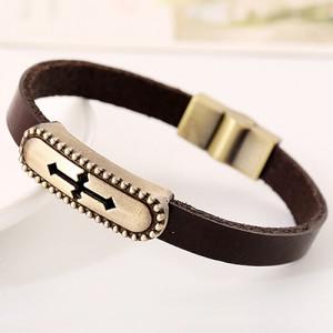 Коричневый браслет из кожи с бронзовой планкой с изображением креста фото. Купить