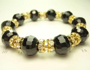 Чёрный браслет «Агата» из гранённых хрустальных бусин на резинке с золотыми вставками купить. Цена 115 грн