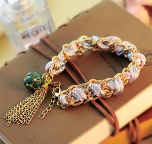 Модный браслет в виде цепи с вплетёнными в неё розовыми и бирюзовыми нитками и зелёным кулоном в форме шара купить. Цена 79 грн или 250 руб.