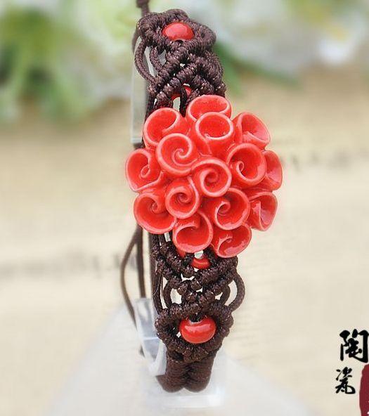 Коричневый плетёный браслет с ярко-красным цветком из керамики купить. Цена 185 грн