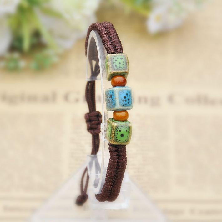 Плетёный из коричневой нити браслет с тремя керамическими разноцветными кубиками купить. Цена 75 грн