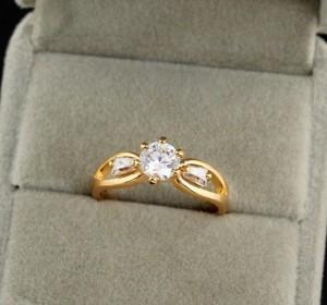Классическое кольцо с тремя фианитами и 18-ти каратным золотым покрытием фото. Купить