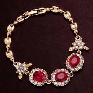 Симпатичный браслет «Примула» с красными камнями, стразами и покрытием под золото фото. Купить