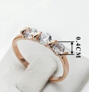 Тоненькое кольцо «Трио» с тремя камнями Сваровски в ряд и розовой позолотой купить. Цена 145 грн