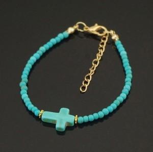 Интересный браслет из мелких бирюзовых бусин с небольшим крестом из бирюзы фото. Купить