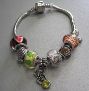 Весёлый браслет «Pandora» с разнообразными бусинами и фенечками фото. Купить