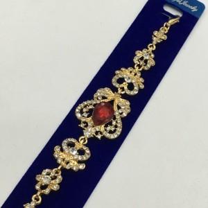 Золотого цвета браслет «Виндзорский» с красным камнем и бесцветными стразами фото. Купить